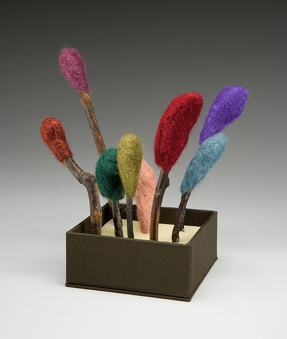camphor sticks wrapped with different color felt at  the ends standing in a small box